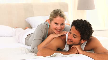 fekvő : Cute couple laying on their bed and they are looking at the camera Stock mozgókép