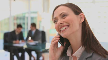 брюнет : Woman dressing in a business suit speaking on the phone