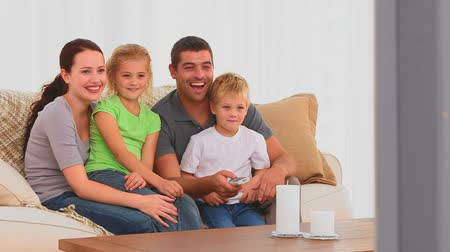 assistindo : Family laughing in front of tv in the living room Vídeos