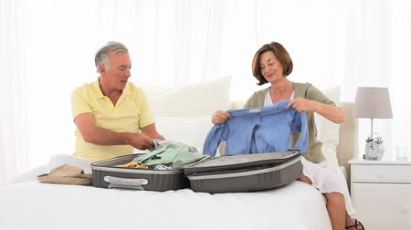 bútor : Mature couple leaving for vacacion and packaging on the bed