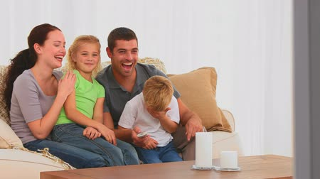 наслаждаться : Smiling family watching a movie in the living room