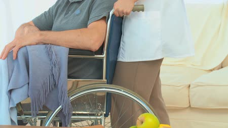 stáří : A patient on a wheelchair with a nurse at the hospital