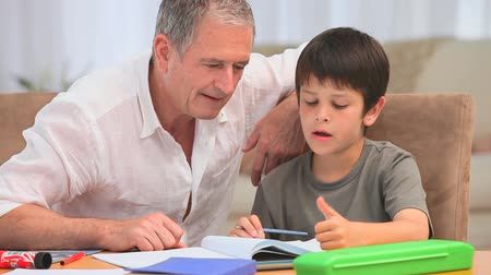 özel öğretmen : Little boy doing his maths homeworks with his grandfather