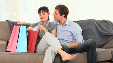 namorado : Woman showing her new clothes to her boyfriend in a sofa