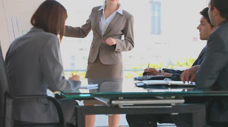 sala de reuniões : Business woman making a presentation in front of business people