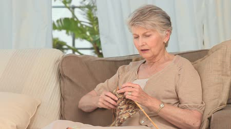 вязание : Retired woman knitting on the couch