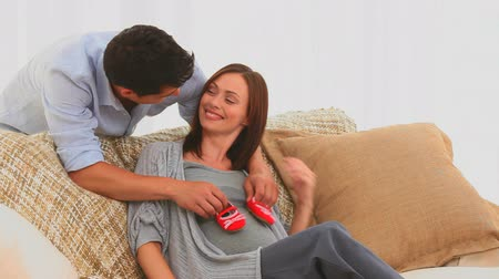 отцовство : Couple playing with baby shoes on the sofa