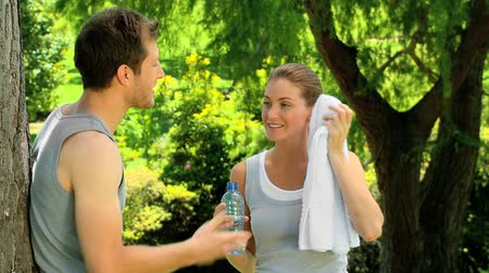 amantes : Atlethic couple relaxing and drinking water under a tree after jogging