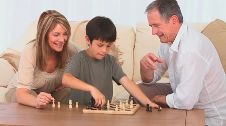 guy home : Little boy playing chess with his grandfather in the living room Stock Footage