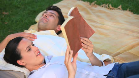 otuzlu yıllar : Woman reading a book to her husband lying on the grass in the park Stok Video