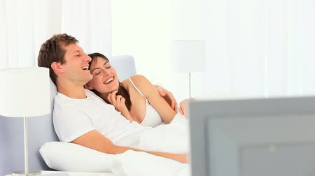 casal heterossexual : Lovely couple watching tv in their bedroom