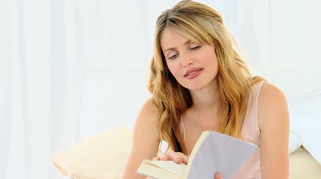 konfor : Pretty blonde woman reading a book at home Stok Video
