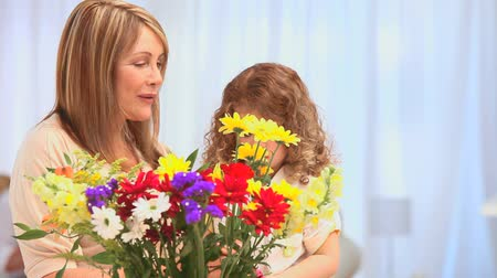 bouquets : Cute little girl making a bunch of flowers with her grandmother Stock Footage
