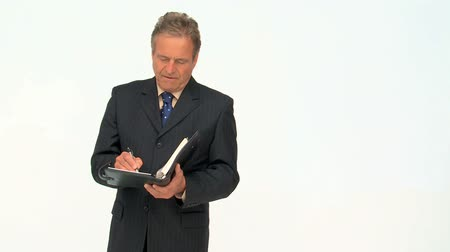 daň : Mature businessman taking notes isolated on a white background