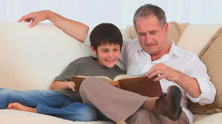 grandchild : Boy looking at an album with his grandfather on the couch