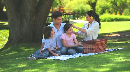 пикник : Happy family eating watermelon while picnicking under a tree