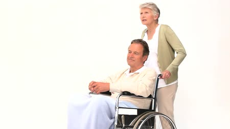 hemşirelik : A man in wheelchair talking with his wife isolated on a white background