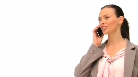 диалог : Radiant woman phoning against a white background Стоковые видеозаписи