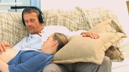 koca : Man putting headphones on the belly of his expecting wife