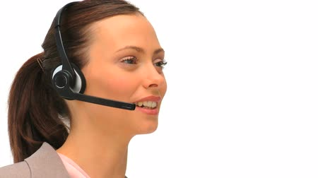 irodaház : Business woman using an headset against a white background Stock mozgókép