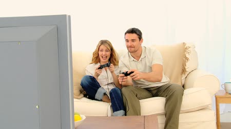 oynamak : Pretty couple playing a video game on their sofa Stok Video