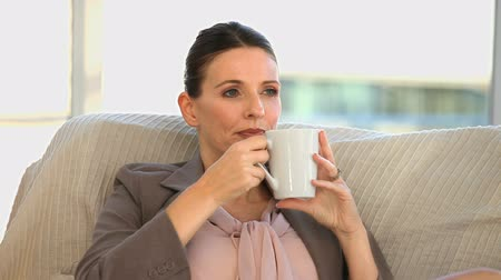 orta : Brunette middle aged lady drinking a cup of coffee on a sofa
