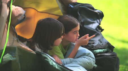 kamp : Cute children in a tent chatting and looking out at something