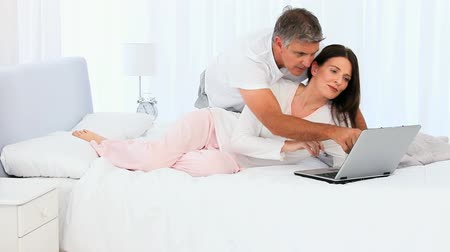 orta : Middle aged couple laughing in front of a laptop on their bed