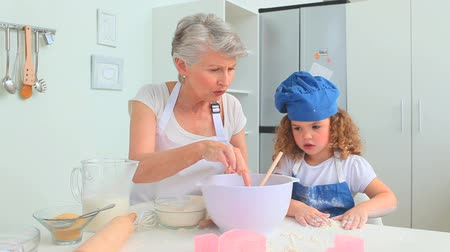 mutfak malzemesi : Cute curly haired girl baking with her grandmother