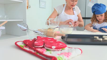 бабушка : Grandmother and her grand daughter baking together in the kitchen
