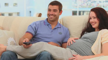 assistindo : Beautiful future parents watching the tv in their couch