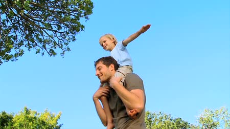 high def : Little boy sitting on his fathers shoulders outdoors in the sunshine