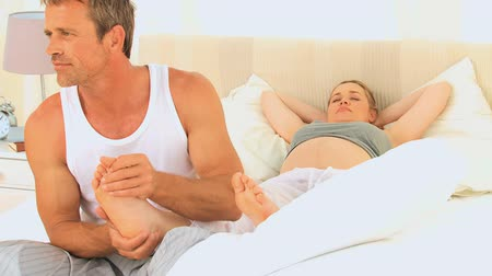 kobiety : Man massaging feet of his pregnant wife on their bed