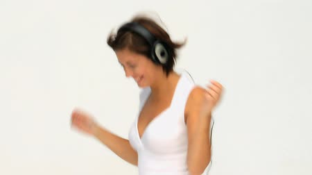 наушники : Attractive woman listening to music against a white background