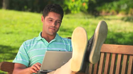 gündelik kıyafetler :  Man relaxing and chatting  on a laptop  sitting on a park bench Stok Video