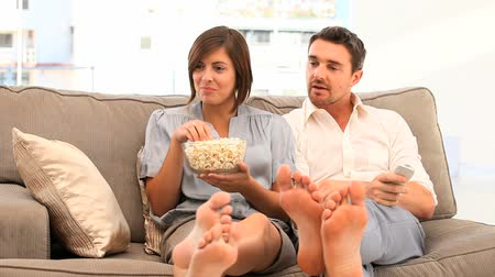 home life : Couple watching tv with popcorn on their couch