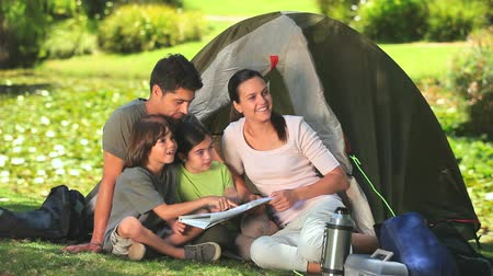 sátor : Parents helping children to read a map while sitting in front of their tent