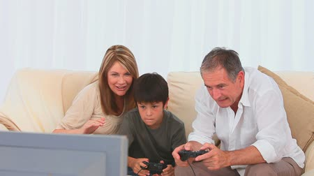 hareketli : Grandparents playing video games with their grandson in the living room Stok Video
