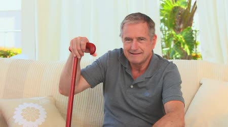 bengala : Retired man using a walking stick in his living room Stock Footage