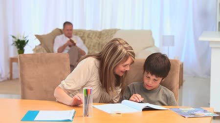 uczenie się : A boy doing his homeworks with his grandmother in the living room Wideo