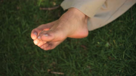 deslizamento : A man twiddling his bare toes