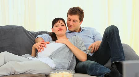 casal heterossexual : Future parents watching tv in their living room