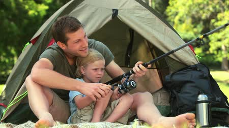 sátor : Father teaching his son how to use a fishing rod outside their tent Stock mozgókép