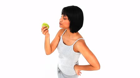 eat background : Casual asian woman enjoying an apple against a white background