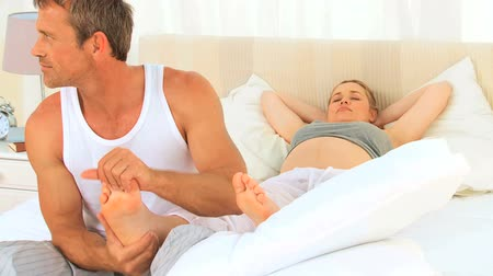 dokunaklı : Pregnant woman letting his husband massaging his feet in the bedroom