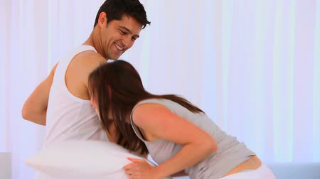 kavga : Happy couple playing with pillows in their bedroom Stok Video