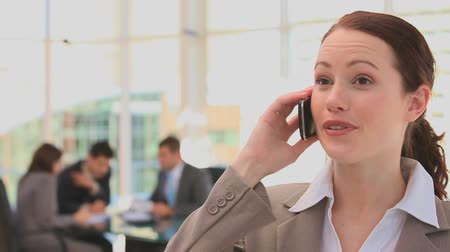 брюнет : Business woman making a phone callwith business people in the background