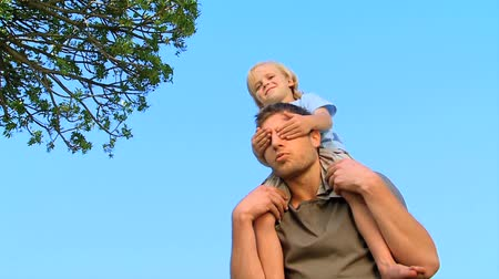 parenthood : Father carrying his son on his shoulders in the park