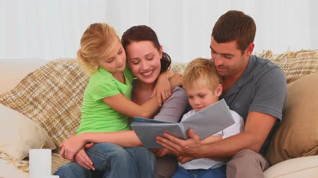 carinho : Family reading a children book on their couch at home