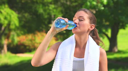 усталый : Woman drinking water and wiping her face after sports in a park